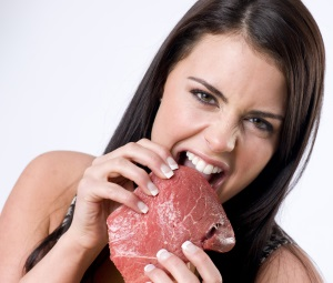 A beautiful young adult woman eats a raw piece of steak