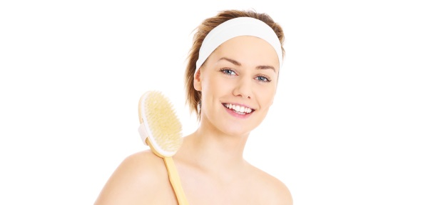 A picture of a woman doing peeling with a brush over white background