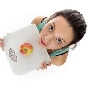 Woman shot from a birds eye view looking down holding scale an an apple