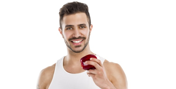 Athletic young man holding a fresh apple, isolated over a white background