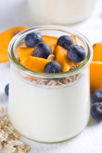 Close up of yogurt in glass jar topped with cut persimmon and blueberries