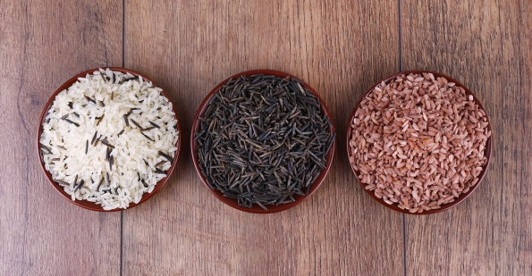 Different kinds of rice on plates on wooden background